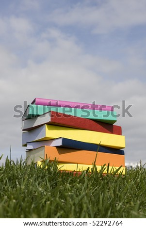 A stack of colorful books on the grass - stock photo