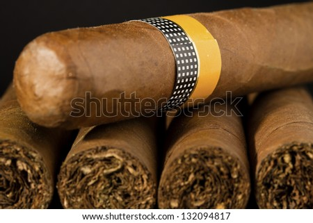 A stack of exclusive Cuban Cigars on black background. - stock photo