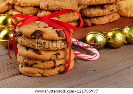 A stack of holiday chocolate chip cookies tied with a red ribbon in front of jingle bells , candy cane, and a platter of assorted baked treats. Horizontal format with shallow depth of field. - stock photo