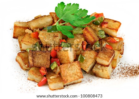 A stack of home fried potatoes with peppers, onions and paprika.  On a white background. - stock photo