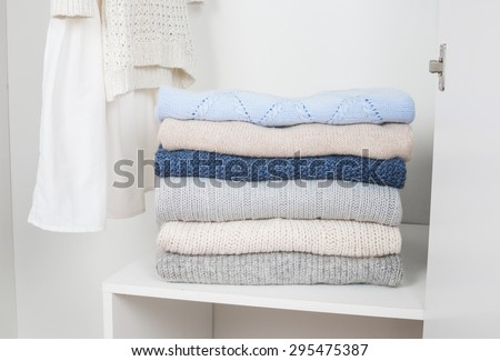 a Stack of knitted warm woolen clothes in white wardrobe close up - stock photo