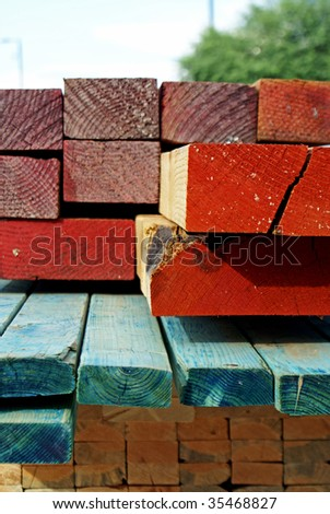 A stack of lumber of varying shapes, sizes and colors, delivered to a construction site - stock photo