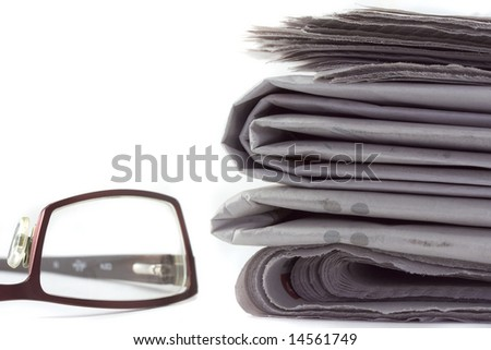 A stack of newspapers with a pair of reading glasses, isolated on white. - stock photo