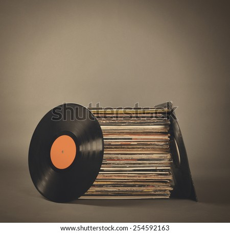 A stack of old retro vinyl records on an isolated gray background for a party or entertainment concept. - stock photo