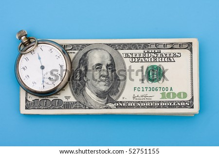 A stack of one hundred dollar bills with a watch on it sitting on a blue background, time is money - stock photo