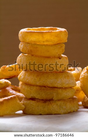 A stack of onion rings on a dark background - stock photo