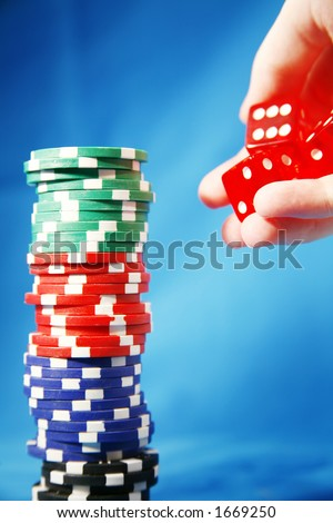 A stack of poker playing chips and rolling die - stock photo