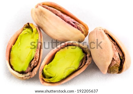 A stack of roasted pistachios on white  . image collected from a few photos for larger areas of focus - stock photo