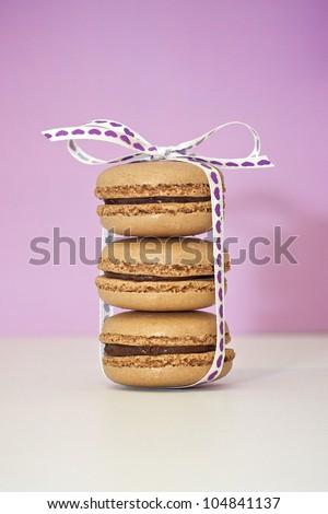 A stack of three chocolate macarons. - stock photo