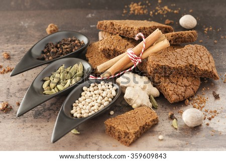 A stack of traditional dutch speculaasbrokken. And spoons filled with spices: cloves, ginger, cardamom, cinnamon, white pepper, nutmeg - stock photo