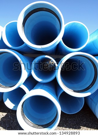 A stack of water pipe at a construction site. - stock photo