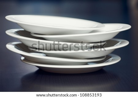 A stack of white plates on a table - stock photo