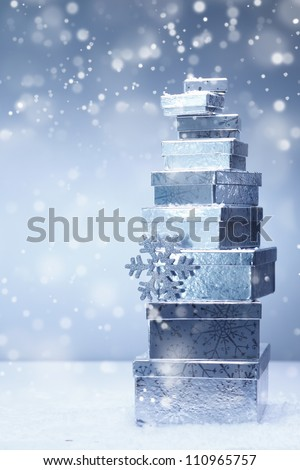 A stacked tower of silver Christmas gifts in diminishing sizes and different angles in falling snow with copyspace - stock photo