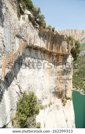 A stairs trail encrusted in a rock over a river - stock photo