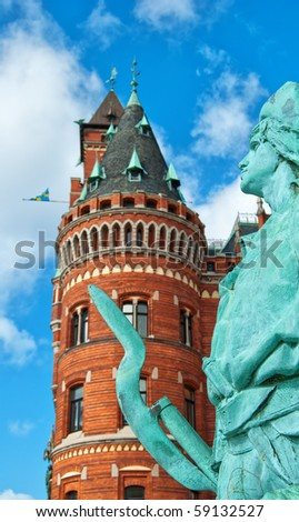 A statue in front of the impressive town hall in Helsingborg with selective focus used to highlight the statue. - stock photo