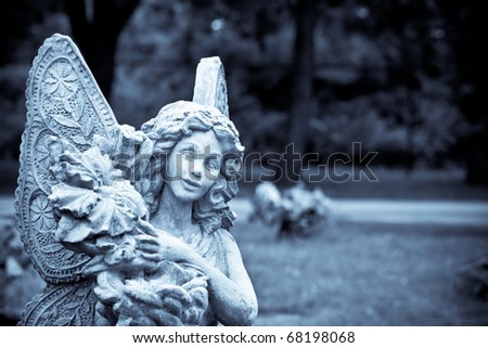 A statue of an angel holding flowers with her wings spread - stock photo