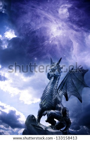 a statue of dragon over stormy magic sky - stock photo