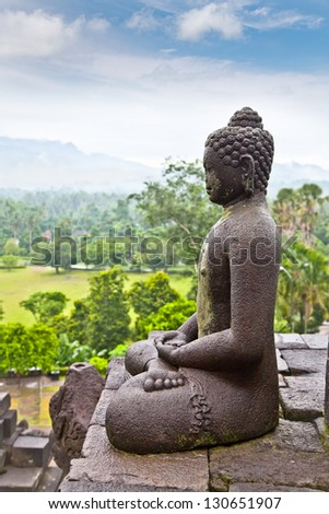 A statue of the Buddha from Borobudur on Java in Indonesia. - stock photo