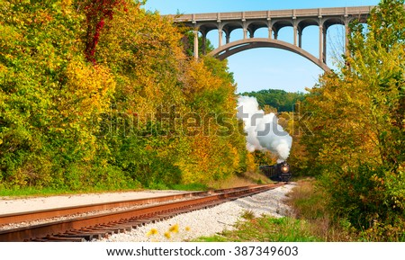 A steam locomotive rounds a curve in the distance under a high arched bridge south of Cleveland, Ohio - stock photo
