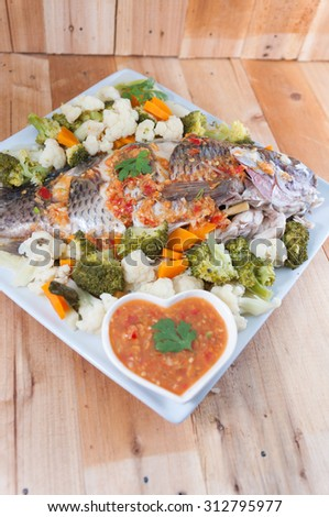 A Steamed Tilapia fish garnish with vegetables.Selective focus. Very shallow Depth of Field, for soft background. - stock photo