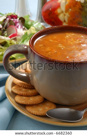 A steaming bowl of hot chicken gumbo and a tossed green salad - stock photo