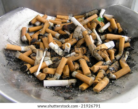 A steel ash tray full of cigarette ends - stock photo
