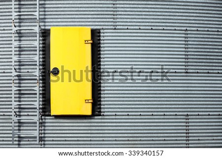 A steel bin adorned with a bright yellow door and ladder. - stock photo