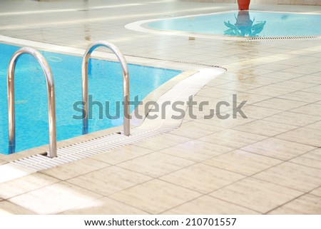 a steps in a blue water pool  - stock photo