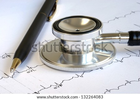 A stethoscope and a pen on the top of the EKG graph - stock photo