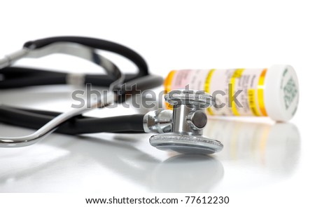 A stethoscope and prescription bottle on a white background with copy space - stock photo