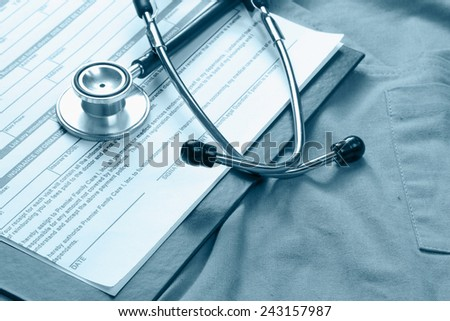 A stethoscope and RX prescription lying on a medical uniform - stock photo