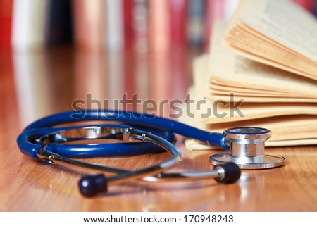 A stethoscope is lying with a book on the desk against books - stock photo