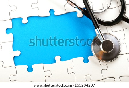 a stethoscope lying on an unfinished puzzle - stock photo