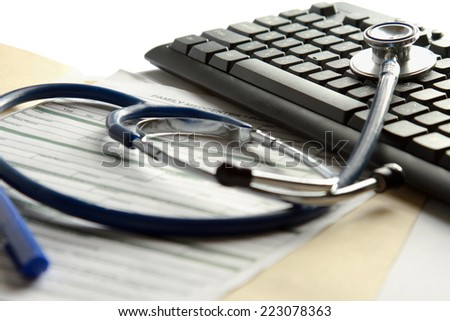 A  stethoscope on a laptop computer. - stock photo