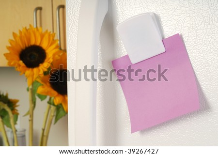 A sticky note reminder placed on the fridge - stock photo