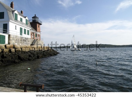 A stiff breeze pushes a beautiful sailboat around the point of Breakwater Lighthouse, Rockland Harbor, Maine. - stock photo