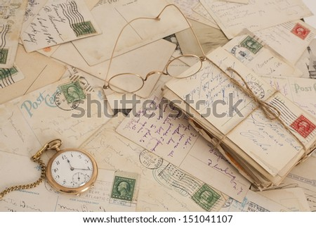 A still life grouping of hundred year old postcards with old stamps and lovely handwritten messages.  To accentuate their age an old time piece and set of eye glasses is set with it. - stock photo