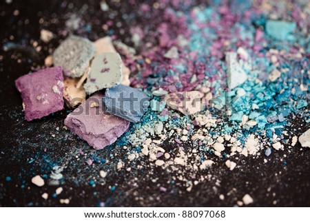 a still-life of colorful eyeshadow powders and make-up - stock photo