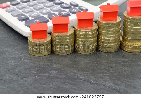 A still life with stacks of pound coins, that have toy houses on top. A metaphor on property finance. - stock photo