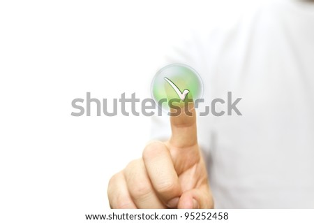A stock photo of a man in a white t- shirt pressing a button green tick with his finger - stock photo