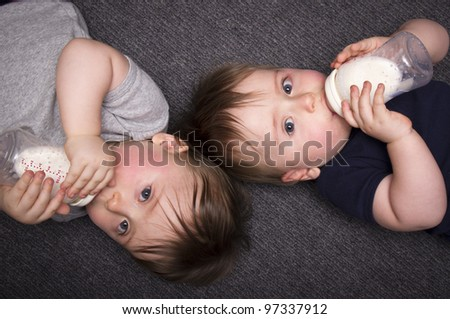 A stock photo of one year old twin boys lying on the ground drinking from bottles - stock photo