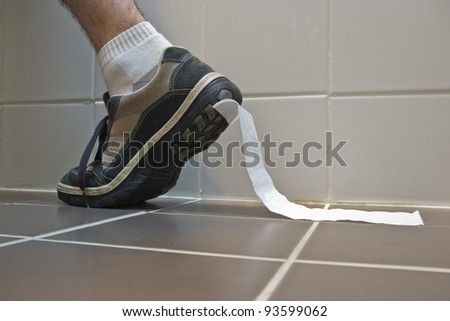 A stock photo of toilet paper stuck to the sole of a sneaker - stock photo