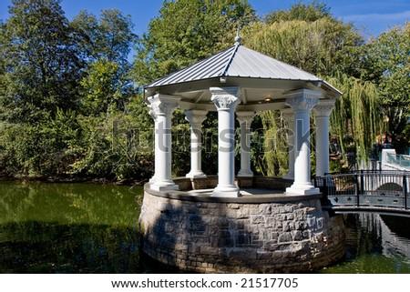 A stone and wood columned gazebo on a peaceful lake - stock photo
