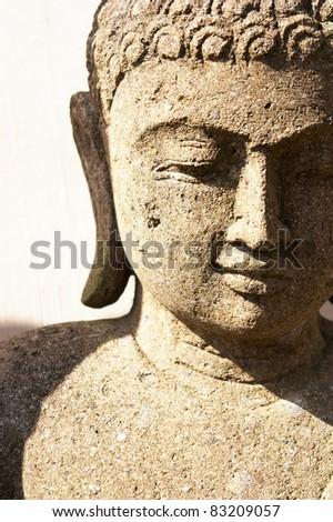 A stone Buddha Statue under bright sunlight. - stock photo