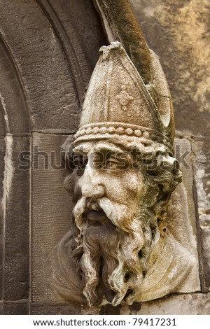 A stone carving of Saint Patrick on the lower door to the Chapel Royal of Dublin Castle in Dublin, Ireland. The stone is discolored with lichen and shows the effect of weather over the years. - stock photo