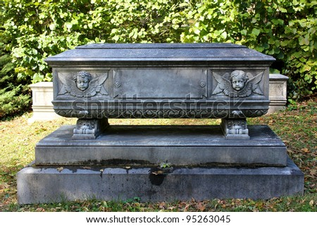 A stone memorial in the shape of a casket, adorned with the faces of two cherubim. - stock photo