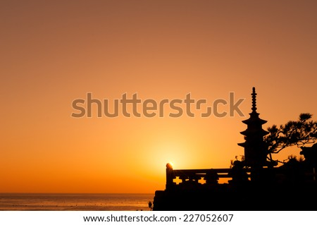A stone pagoda stands in silhouette against an orange sunrise at Haedong Yonggungsa Temple in Busan, South Korea. - stock photo