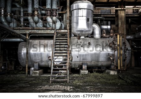 A storage tank inside an old abandoned factory - stock photo