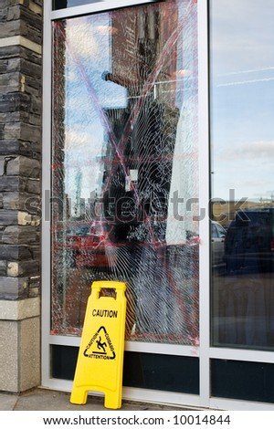 A store window that was broken, and looks like a spiderweb. - stock photo