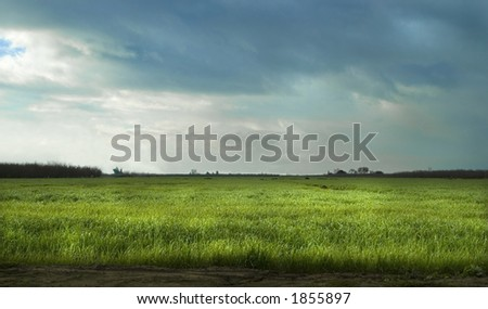A storm approaches a field. - stock photo
